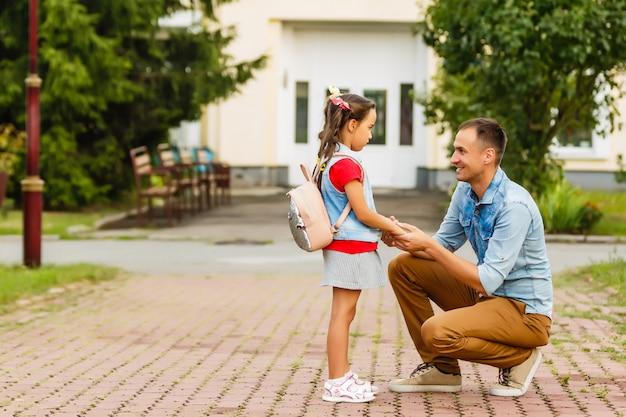 Primeiro dia na escola. pai lidera uma criança pequena menina da escola em primeiro lugar