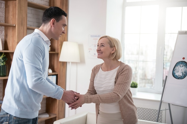 Primeiro encontro. mulher sênior alegre e homem sorrindo enquanto apertam a mão