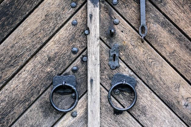 Primeiro plano da porta de madeira velha com punho do ferro. punho oxidado velho da porta na porta de madeira.