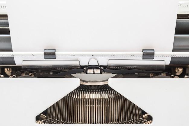Primeiro plano de máquina de escrever vintage em fundo branco esperando por você para escrever seu melhor romance.
