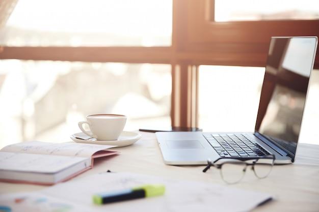 Primeiro plano lateral de uma mesa de trabalho com o laptop, xícara de café, óculos e artigos de papelaria