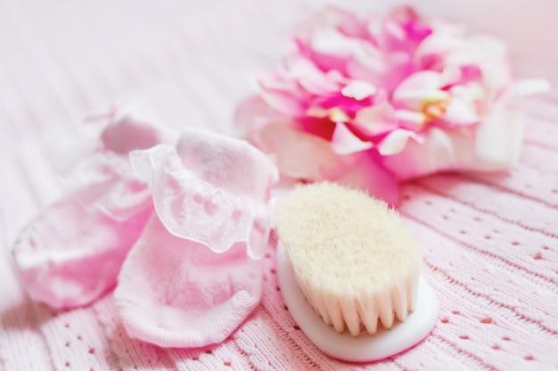 Primeiros acessórios para menina recém-nascida - botinhas cor de rosa, chapéu com flor de seda e minúscula escova de cabelo.
