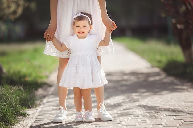 Primeiros passos do bebê. criança tentando andar. mãe e sua pequena filha adorável segurando pelas mãos. mãe irreconhecível e sua filha usando tênis ou keds