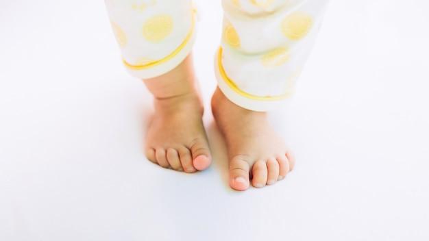 Primeiros passos do bebê recém-nascido, pés de criança no chão branco