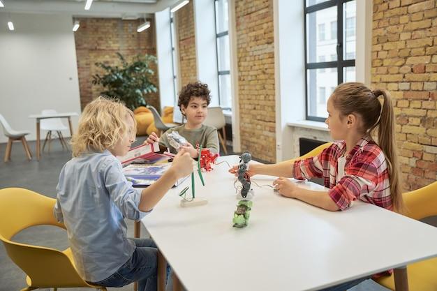 Primeiros passos na aprendizagem de crianças curiosas e diversificadas, discutindo e examinando brinquedos técnicos cheios de