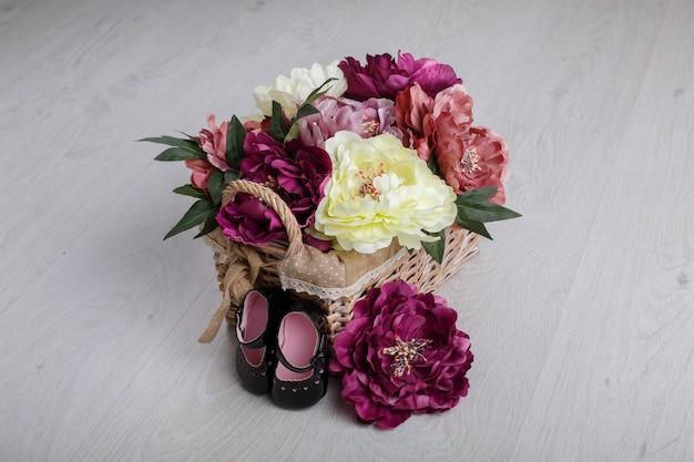 Primeiros sapatos para princesinha isolada na mesa de luz com espaço para texto. sapatos de bebê de couro preto com flores de cesta de vime. sapatos elegantes para menina recém-nascida para os primeiros passos fechar.