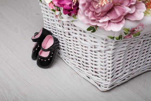 Primeiros sapatos para princesinha isolada na parede de luz com espaço para texto. sapatos de bebê de couro preto com flores de cesta de vime. sapatos elegantes para menina recém-nascida para os primeiros passos fechar.