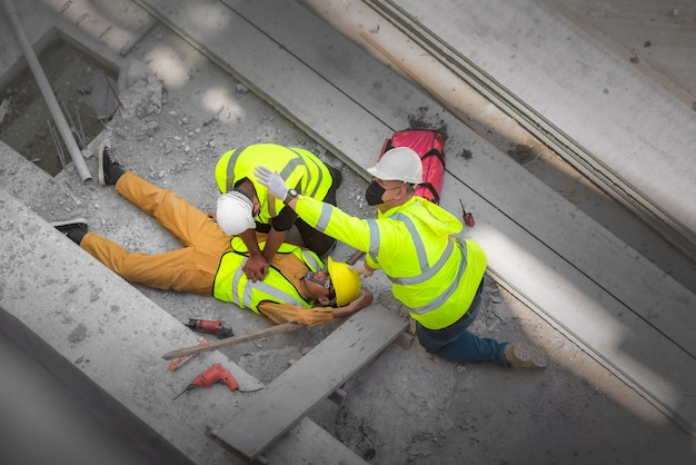 Primeiros socorros básicos e rcp para acidentes de emergência em canteiros de obras. trabalhador da construção civil ficou ferido em uma queda de altura no canteiro de obras. equipe de segurança e engenheiros ajudam a realizar os primeiros socorros