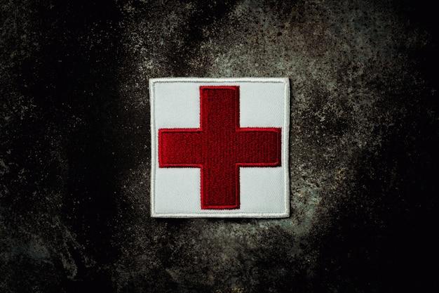 Primeiros socorros cruz vermelha bandeira na placa de metal enferrujada abandonada.