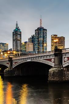 Princes bridge e edifícios da cidade no rio yarra em melbourne, austrália à noite