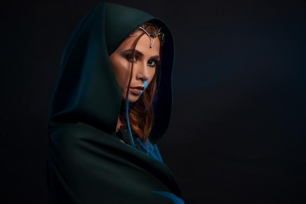 Princesa elfa bonita vestindo capa verde escura, olhando para a câmera da escuridão.