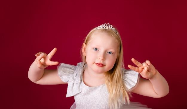 Princesa loira pequena bonita dançando no vestido branco e prata de luxo isolado em fundo vermelho. cara engraçada, emoções diferentes