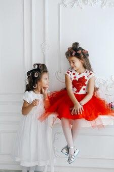 Princesas pequenas em rolos de cabelo, olhando um ao outro e sorrindo