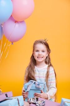 Princesinha bonita com cabelo comprido segurando uma caixa de presente enquanto está sentada na parede amarela