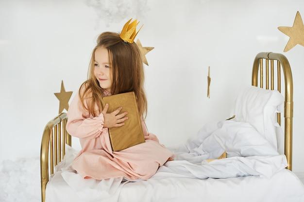 Princesinha com uma varinha mágica em uma cama em uma nuvem em um fundo branco