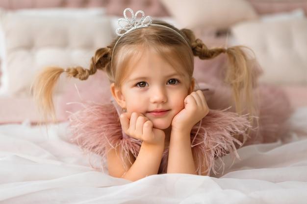 Princesinha em um vestido de noite está deitado em uma cama linda