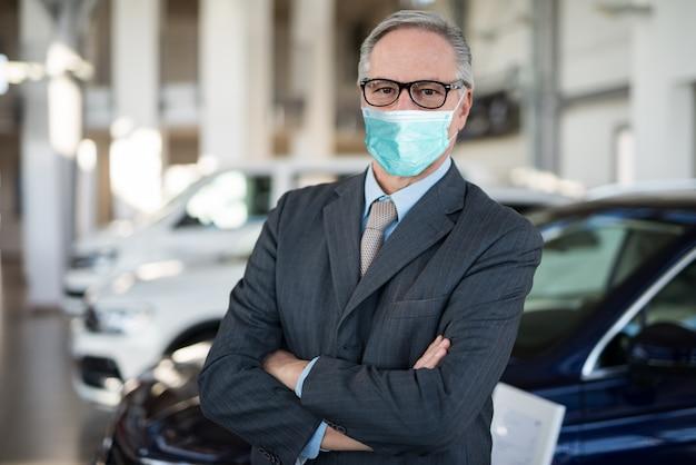 Principal do revendedor de carros dentro da sala de exposições durante a pandemia de coronavírus