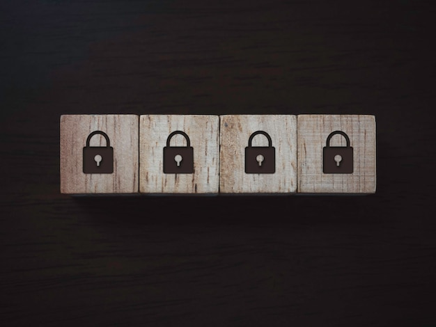 Privacidade e conceito de proteção de dados pessoais. ícone de quatro cadeado em blocos de madeira em fundo escuro de madeira, vista superior. segurança de senha.