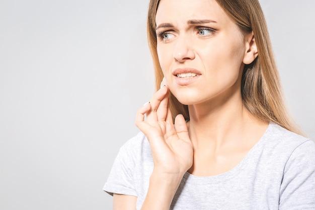 Problema de dentes. mulher que sente a dor de dente. close da bela garota triste, sofrendo de forte dor de dente. mulher atraente, sentindo dor de dente dolorosa. saúde bucal e conceito de cuidados. alta resolução