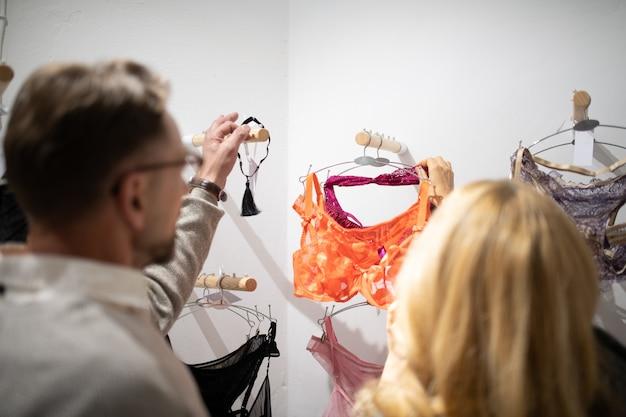 Problema de escolha. marido e mulher em frente a cabides com roupas íntimas diferentes na loja de lingerie.