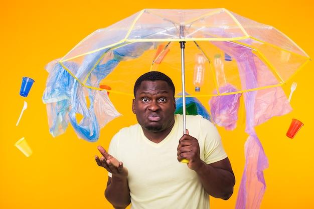 Problema de lixo, reciclagem de plástico, poluição e conceito ambiental - homem afro-americano pensativo na parede amarela com lixo.