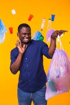 Problema de lixo, reciclagem de plástico, poluição e conceito ambiental - homem confuso carregando