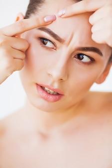 Problema de pele. mulher esmagando o ponto no rosto e olhando no espelho