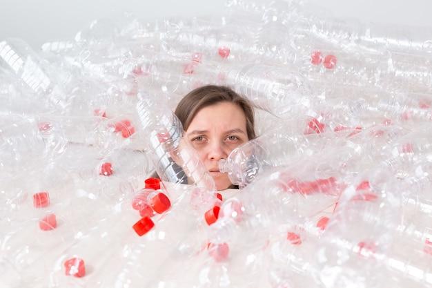 Problema de poluição de plástico e proteção do meio ambiente. mulher fraca e cansada em uma pilha de garrafas plásticas. salve o conceito de terra. limpe nossa natureza.