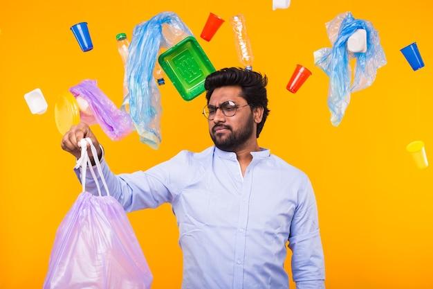 Problema de reciclagem de plástico, ecologia e conceito de desastre ambiental - homem indiano olhando para o lixo com nojo na parede amarela.