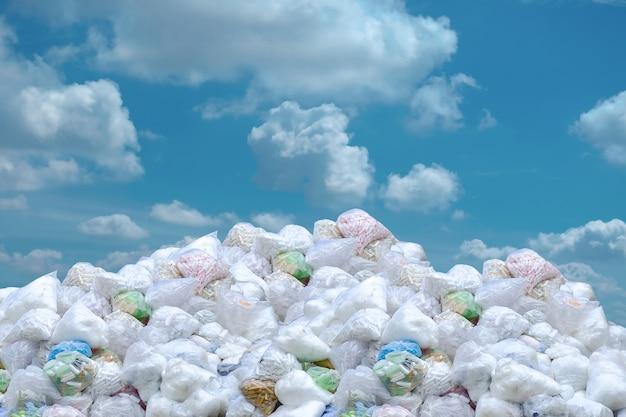 Problema global do lixo, pilha do saco de plástico e garrafas.