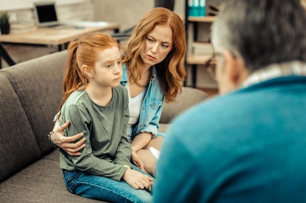 Problema psicológico. menina simpática e triste sentada no sofá enquanto sofre de autismo