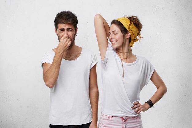 Problemas com odor corporal. homem enojado apertando o nariz sentindo mau cheiro ou fedor saindo de uma garota atraente e sorridente, que está levantando o braço, mostrando a camiseta molhada por causa do suor nas axilas