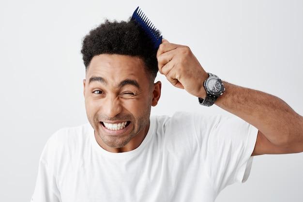Problemas de cabelo encaracolado. feche de bonito americano de pele negra jovem com corte de cabelo afro em camiseta branca casual, penteando o cabelo, olhando na câmera com a expressão do rosto engraçado.