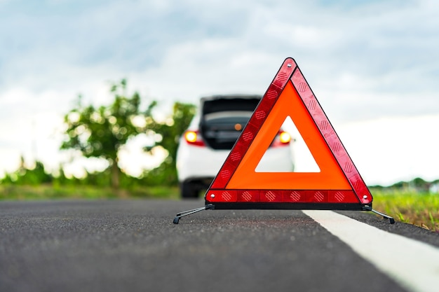 Problemas de carro e um sinal de aviso vermelho triângulo na estrada