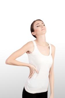 Problemas de saúde. close up da jovem mulher bonita que tem a dor nas costas, dor traseira forte. fêmea que sofre do sentimento doloroso nos músculos, guardando as mãos em seu corpo. conceito de cuidados de saúde.
