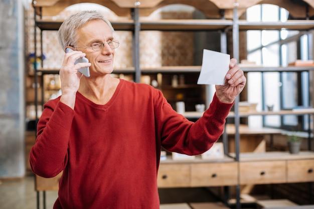 Problemas de trabalho. homem idoso encantado positivamente segurando um bilhete e fazendo uma ligação enquanto quer discutir alguns problemas de trabalho