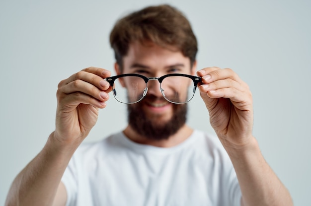 Problemas de visão de homem barbudo em fundo claro de camiseta branca