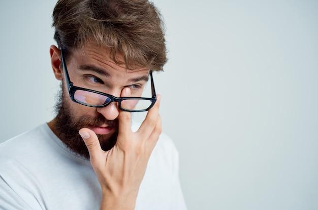 Problemas de visão de homem barbudo em fundo isolado de t-shirt branca. foto de alta qualidade