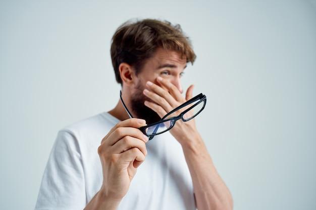 Problemas de visão de homem barbudo na luz de fundo de t-shirt branca. foto de alta qualidade