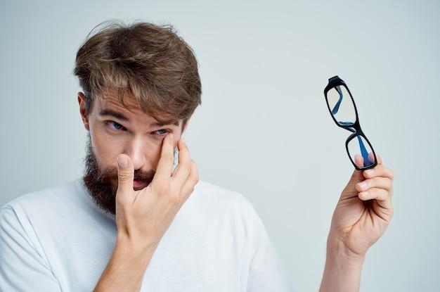 Problemas de visão de homem em fundo isolado de camiseta branca