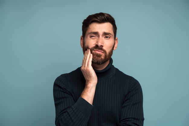 Problemas dentários. retrato de homem insalubre pressionando a bochecha dolorida, sofrendo de dor de dente aguda, doença periodontal, cáries ou dor na mandíbula. foto de estúdio interna isolada em fundo azul