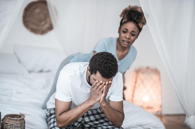 Problemas, família. homem infeliz de pele escura de pijama cobrindo o rosto com as mãos sentado na cama e esposa preocupada