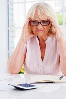 Problemas financeiros. mulher sênior frustrada segurando a cabeça nas mãos e olhando para as notas sobre a mesa