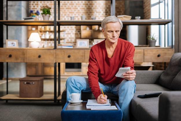 Problemas financeiros. sério e agradável homem aposentado sentado à mesa de centro e tomando notas enquanto conta suas economias