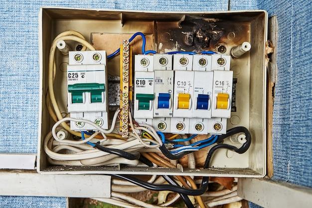 Problemas na chave de segurança, quadro elétrico antigo queimado e disjuntores localizados em prédio residencial.