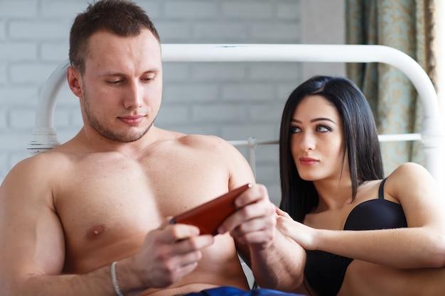 Problemas na família. jovem furiosa deitada na cama, contra o marido, que joga o jogo ao telefone.