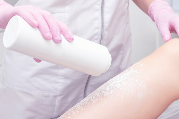 Procedimento cosmético aplicando talco na depilação dos pés