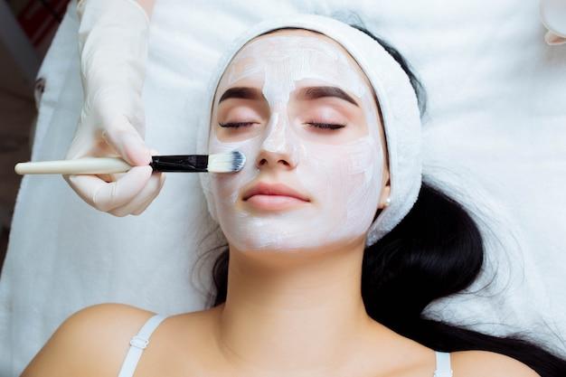 Procedimento cosmético facial em salão de spa o procedimento para aplicar uma máscara no rosto de uma ...