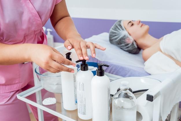 Procedimento cosmético facial no salão spa. o procedimento para aplicar uma máscara no rosto de uma mulher bonita