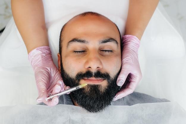 Procedimento cosmético para aumento dos lábios e remoção de rugas em um homem barbudo. cosmetologia.